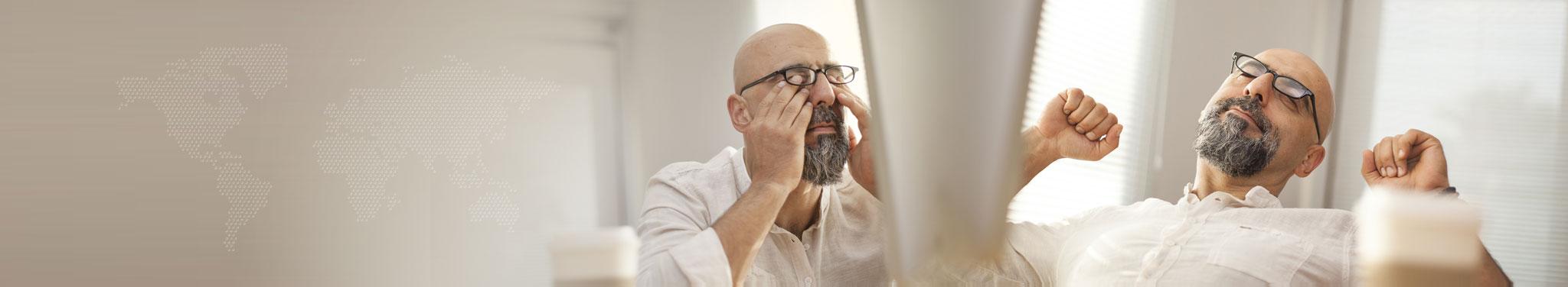 Müder Mann mit Bart, Brille und Glatze